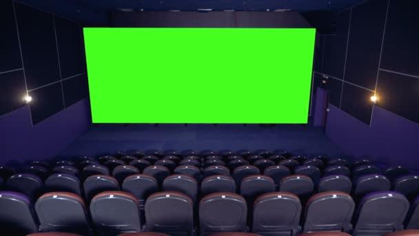 dunkler leerer Kinosaal mit grüner Leinwand.