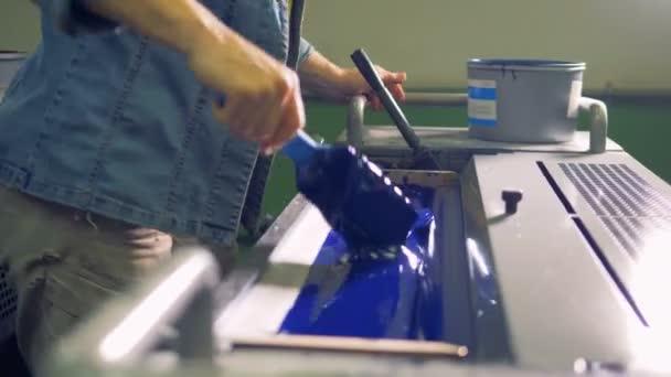Zaměstnanec se připravuje modré barvy v průmyslové tiskové stroje