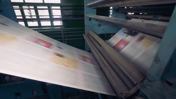 Fresh daily newspapers rolling on a printing equipment. 4K.