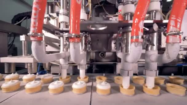 Four industrial pipes are filling moving wafer cups with ice-cream substance