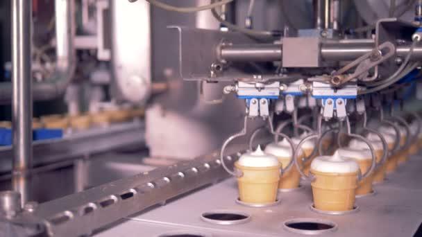 Dva řádky zmrzlinové poháry se pohybují podél kovový dopravní pás a zvedají a odsátím kleště