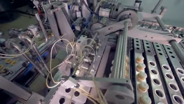 Factory mechanism is displacing wafer cups with ice-cream from a straight conveyor belt to a descending one