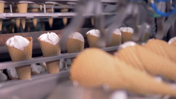 Zmrzlinových kornoutů jsou právě přemístěna z rotačním dopravníkem pro jednu lineární
