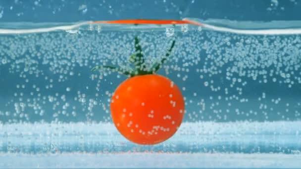 Jediné rajče klesá do nádrže zpola plná s vodou