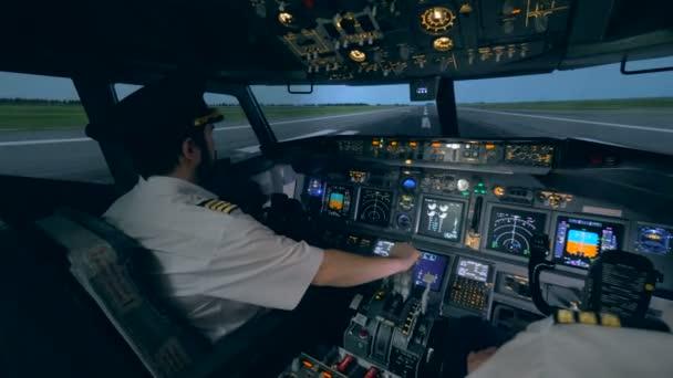Zwei Piloten sind in einem Cockpit, während ein Flugzeug auf einem Laufsteg geht. 4k.