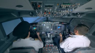 Two pilots turn the plane in a flight simulator.