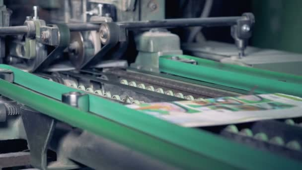 Colourful printed newspapers are getting their edges cut off by a factory mechanism