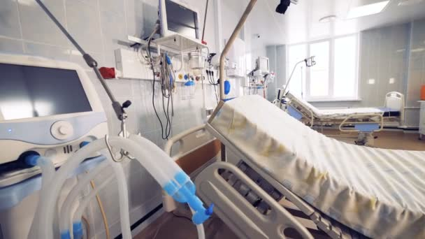 Medical equipment for patients is near hospital bed in emergency room.