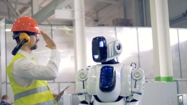 Emberi gyári munkás és egy android egymásnak egy Szia-öt egy feldolgozó létesítmény.