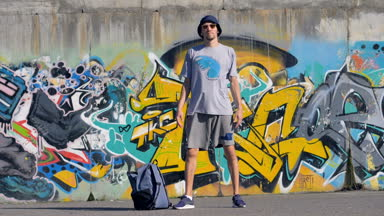 Portrait Of A Male Artist Is Standing In The Street With Graffiti Painting