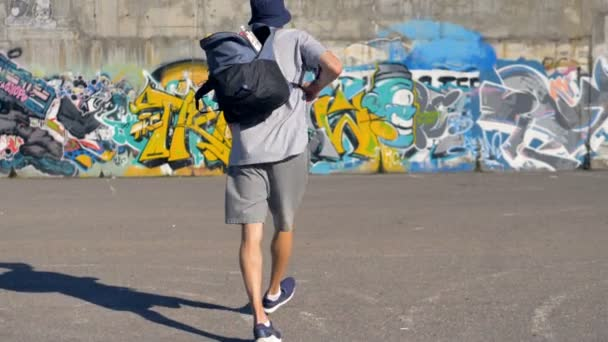 Graffiti művész emelés a hátizsákot, festék-kanna, és megy a graffiti fal felé