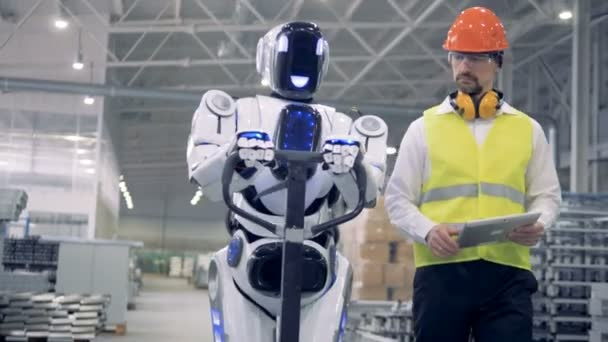 Cyborg is moving a transporting tool along the factory unit while being regulated by a male worker