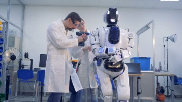 Two technicians are making adjustments to a human-like robot with a drill