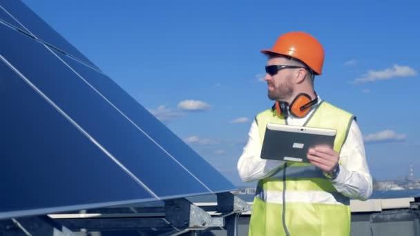 Pracovník kontroly panely na střeše. Inženýr se zabývá sluneční panely kvalita