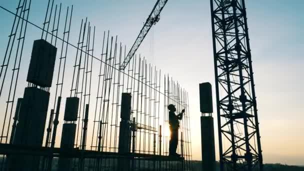 Staveniště s jeřáby a inženýr pracující s kovem