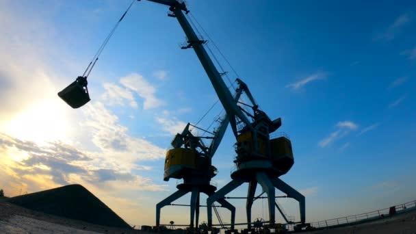 Průmyslové pracoviště při západu slunce s pracovními nakládacími stroji