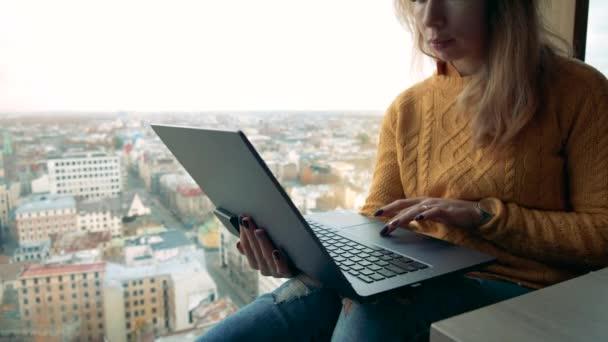 Egy fiatal nő laptoppal, aki a városra néz. Fiatal női szabadúszó laptoppal.