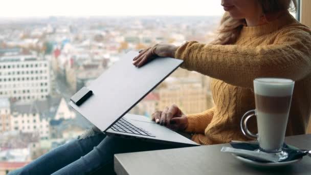 Egy üzletasszony ül szemben a városnézéssel laptoppal.