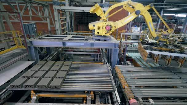 Tovární stroj přesouvá cihlové palety v zařízení.
