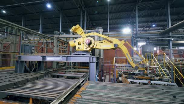 Moderne Fabrikmaschine bewegt Ziegel von einem Förderband in einer Anlage.