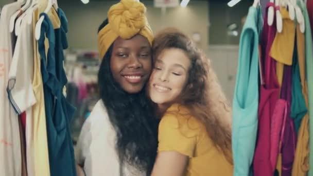 Přední pohled na dvě veselé ženy v obchodě s oblečením