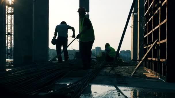 A munkások vezetéket válogatnak az építkezésen.