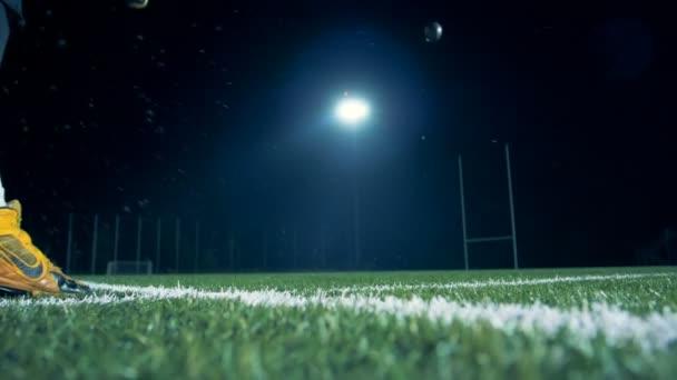 Amerikai focista rugdossa a labdát, közelről.