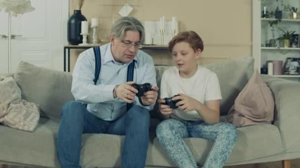 Ein Junge und sein Opa beobachten Konsolensteuerknüppel