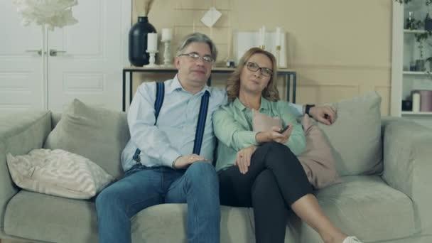 Öreg férfi és nő beszélgetnek miközben TV-t néznek.