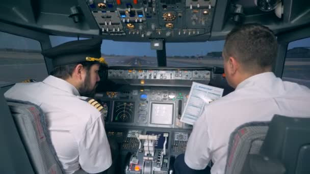Piloten betrachten Papier mit Anleitung, Rückseite.