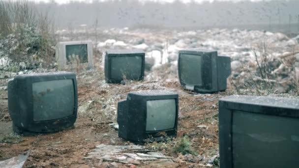 Fekete TV-k dobott egy roncstelepen télen.