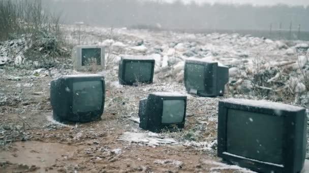 Régi TV-k egy szeméttelepen hóban.