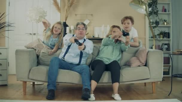 Grandmother, grandfather and their grandkids are playing videogames