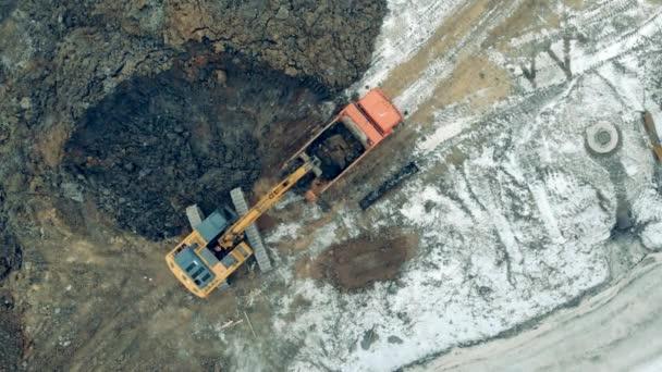 Ein Traktor belädt einen Lastwagen mit Sand. Schwere Maschinen auf einer Baustelle.