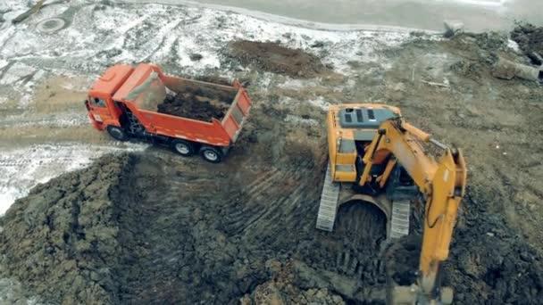 Luftaufnahme von oben von einer Baustelle mit Baggern und Lastwagen. Ein Lader füllt Steine und Sand in einen LKW.