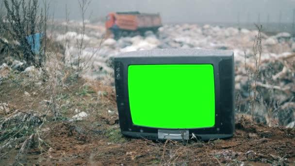 Tv zöld képernyős a hulladéklerakó helyén, miközben havazik