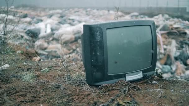 Törött TV egy szemétlerakóval a háttérben