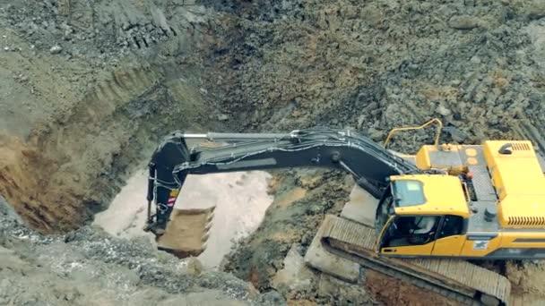 Ein Traktor schüttet Sand in eine Grube.