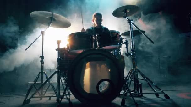 Mužský bubeník hraje na bicí soupravu ve stínu a kouři