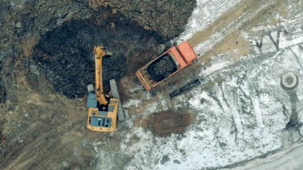 Industrial digger is excavating soil in a top view