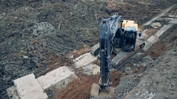 Průmyslový kopáč hloubí půdu v lomu