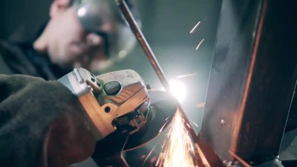 Rotační pila v rukou řemeslníka řeže železo