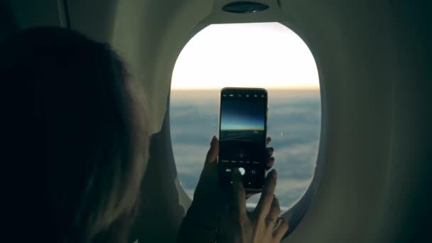 Egy mobiltelefon női kezekben, miközben képeket készítenek a repülőn.