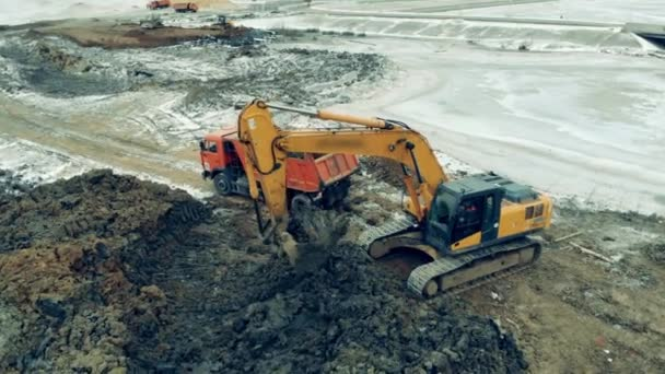 Excavator loads a truck while working at a quarry.