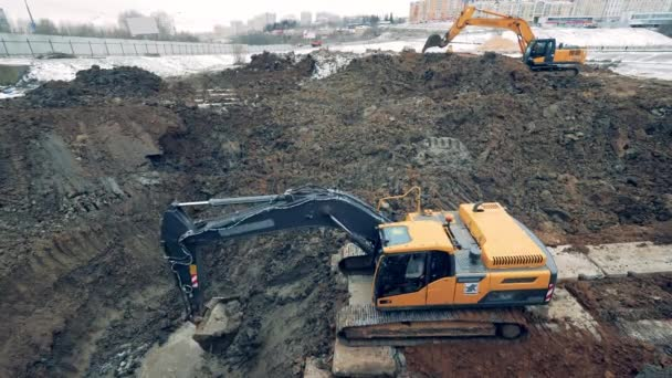 Machines dig earth at a quarry, moving it. Construction excavator work at the industrial quarry.