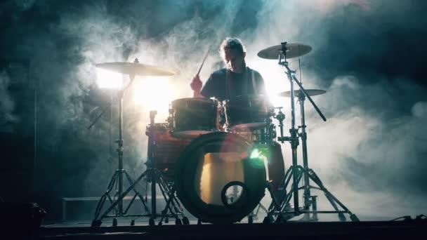Temné studio s bílým kouřem a mužem hrajícím na bicí. Bubnová souprava, bicí souprava v tmě, bubeník hraje na koncert.
