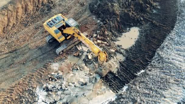 Baggerfahrzeug greift und verschiebt Erde am Steinbruch Gebäude, Bauprozess.