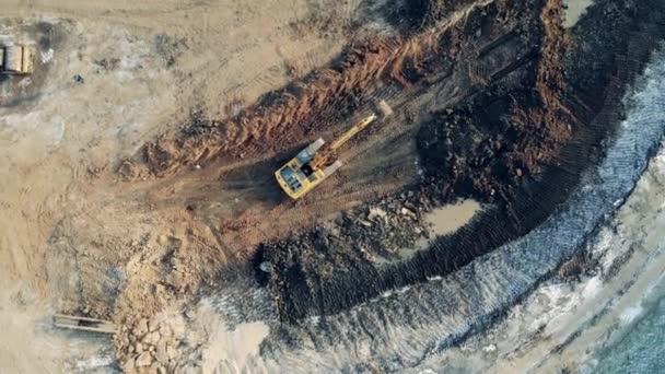 Großes Steinbruchgelände mit einem Baggerfahrzeug in einer Draufsicht. Schwere industrielle Ausrüstung funktioniert.