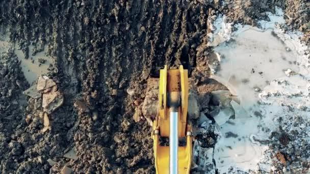 Bauen, Bauen. Baggerschaufel greift sich Erde und knackt Eis