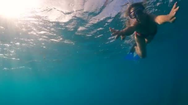 Eine Frau schwimmt unter Wasser und blickt in die Kamera